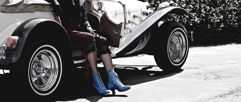 Woman with fishnet stockings sitting in a vintage car with short blue leather Jacquelyn boots