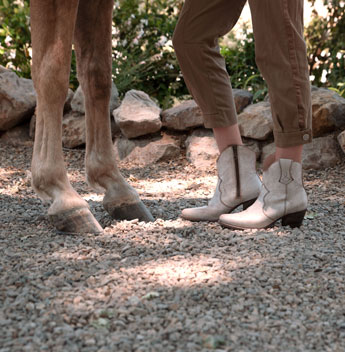 Knee down of a woman wearing tan pants and Oak Tree Farm's Baila Nectar Lux short boots, standing on gravel next to a horse.